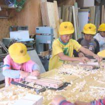 カンナで箸をけずる競争をする児童たち