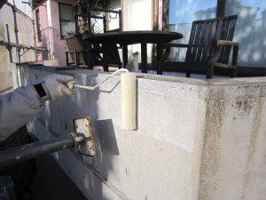 職人が外壁をローラーを使用して塗装している