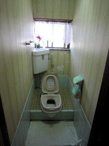 リフォーム前のトイレ。和式に無理やり便座を付けたタイプとなっており不便であった。